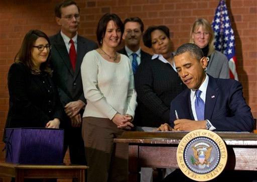 President Barack Obama signs the $1.1 trillion spending bill that funds the federal government through the end of September, in Washington, Friday, Jan. 17, 2014 at Jackson Place, a conference center near the White House. (AP)