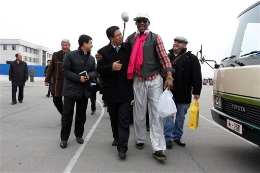Former NBA basketball star Dennis Rodman, second right, walks with North Korea's Sports Ministry Vice Minister Son Kwang Ho, third right, upon his arrival at the international airport in Pyongyang, North Korea, Monday, Jan. 6, 2014.