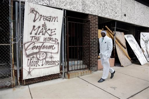In this Thursday, Jan. 16, 2014 photo, Melvin White, founder of the Beloved Streets of America project, walks past a boarded up building during a tour of Dr. Martin Luther King Jr. Drive in St. Louis.