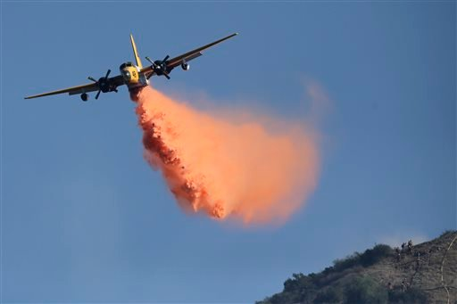 An aircraft drops fire retardant on the Colby Fire on Friday, Jan. 17, 2014, near Azusa, Calif. (AP Photo/Jae C. Hong)