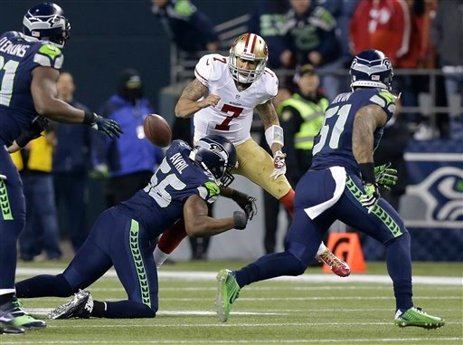 San Francisco 49ers' Colin Kaepernick fumbles as he is hit by Seattle Seahawks' Cliff Avril during the second half of the NFL football NFC Championship game Sunday, Jan. 19, 2014, in Seattle. (AP Photo/Elaine Thompson)