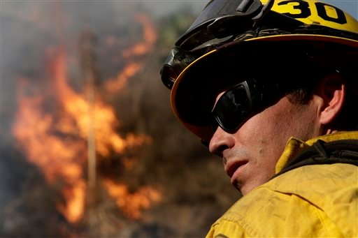 Firefighter Jeff Newby watches a fire burn as he battles the Colby Fire on Friday, Jan. 17, 2014, near Azusa, Calif.