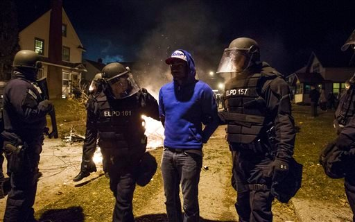 FILE - In this Dec. 8, 2013, file photo, members of the Michigan State Police Department arrest a man in East Lansing's Cedar Village after the Michigan State football team's Big Ten title win prompted rowdy fans to celebrate with bonfires. (AP)