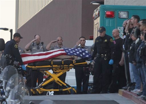 Law enforcement officers salute as the body of a Bay Area Rapid Transit police officer draped with the American flag is loaded into an Alameda County Sheriff's Coroner vehicle at Eden Medical Center in Castro Valley, Calif., Tuesday, Jan. 21, 2014. (AP)