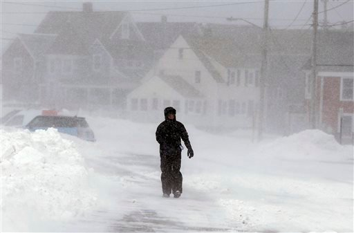 A passer-by walks through snow and strong wind along an empty street in Marshfield, Mass., Wednesday, Jan. 22, 2014. Temperatures across the state were in the single digits early Wednesday. (AP Photo/Steven Senne)