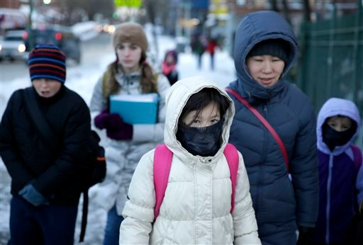 Parents and children arrive to school bundled up against the cold in the Brooklyn borough of New York, Wednesday, Jan. 22, 2014. (AP Photo/Seth Wenig)