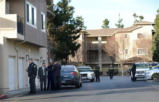 Law enforcement officers investigate the accidental fatal shooting of a Bay Area Rapid Transit police officer by a fellow BART officer while serving a warrant at an apartment building, according to officials, Tuesday, Jan. 21, 2014, in Dublin, Calif. (AP)