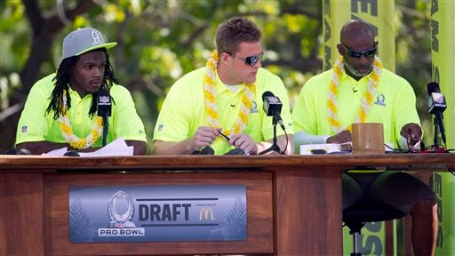 Kansas City Chiefs running back Jamaal Charles, left, Houston Texans defensive end J.J. Watt, center, and Hall of Famer and alumni team captain Deion Sanders, right, check their notes during day two of the 2014 Pro Bowl Draft, Wednesday, Jan. 22, 2014.