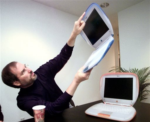 "FILE - In this Wednesday, July 21,1999 file photo, Steve Jobs, Founder and acting CEO of Apple Computer Inc., holds up one of the company's new consumer laptops called an ""iBook"" after his keynote address at the Macworld Expo in New York. (AP)"