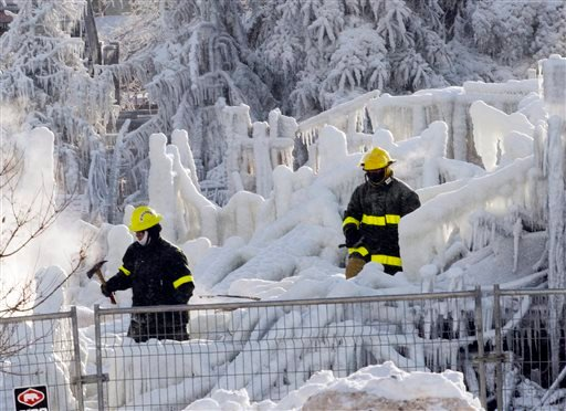 Rescue personnel search through the icy rubble of fire that destroyed a seniors' residence Friday, Jan. 24, 2014, in L'Isle-Verte, Quebec.