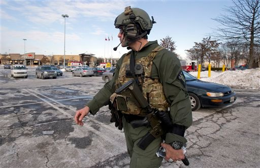 A Montgomery County, Md., police officer walks in a parking lot at The Mall in Columbia, Saturday, Jan. 25, 2014, in Columbia, Md., following a shooting that police say three people died at the mall including the presumed gunman.