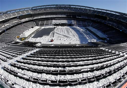 In this photograph taken with a fisheye lens, snow is accumulated on the seats and on the field of MetLife Stadium as crews removed snow ahead of Super Bowl XLVIII following a snow storm, Wednesday, Jan. 22, 2014, in East Rutherford, N.J.