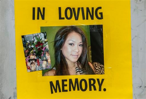 A picture of Kim Pham is among the items placed at a make-shift memorial Friday, Jan. 24, 2014, for Pham, who was beaten to death in front of The Crosby nightclub in Santa Ana, Calif.