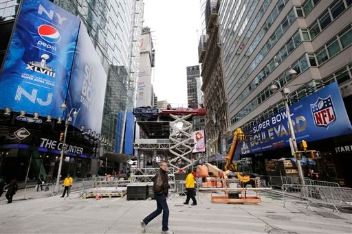 A pedestrian passes a soundstage under construction in New York's Times Square, Sunday, Jan. 26, 2014. (AP)