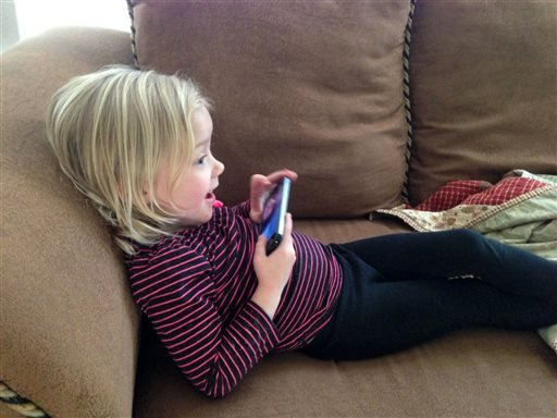 In this January 2014 photo provided by Brandi Koskie, her daughter, Paisley, 3, uses Facetime at her home in Wichita, Kansas to chat with her cousin, who lives in Oklahoma.