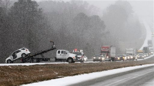 Traffic backs up as a wrecker pulls a car out of a ditch on I-65 during an unual snow Jan. 28, 2014 in Clanton, Ala. A rare storm left a slippery layer of ice and snow across a region unaccustomed to dealing with the wintry threat. (AP Photo/Butch Dill)