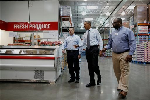 President Barack Obama walks with Ricky Banner, assistant general manager, right, and Emile (Ray) Quevedo, floor employee, at a Costco store in Lanham, Md., Wednesday, Jan. 29, 2014, before he spoke about raising the minimum wage. (AP)
