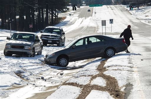 Richard Uzoma returns to his car after he lost control and abandoned it overnight along with other vehicles which couldn't traverse the ice build up on Peachtree Industrial Blvd. Wednesday, Jan. 29, 2014, in Norcross, Ga. (AP)