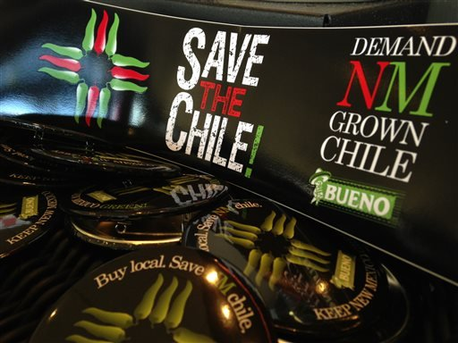 In this July 31, 2013 image, a collection of bumper stickers and buttons promoting New Mexico-grown chile sits on the order counter at Hello Deli restaurant in Albuquerque, N.M. (AP)