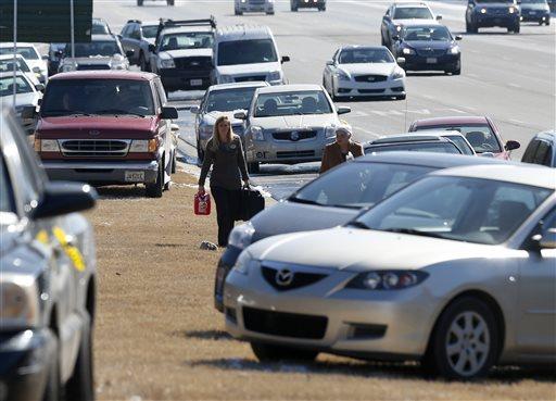 Karen Hurst, left, carries a gas can as she helps Ann Batsun, recover her car on Interstate 75 Thursday, Jan. 30, 2014, in Atlanta. (AP)
