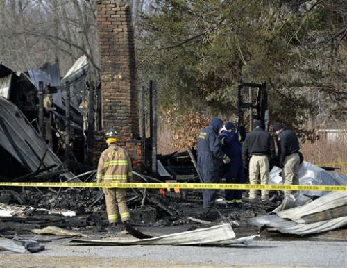 Kentucky State Fire investigators work at the scene of early morning house fire in Depoy, Ky. Thursday Jan. 30, 2014.