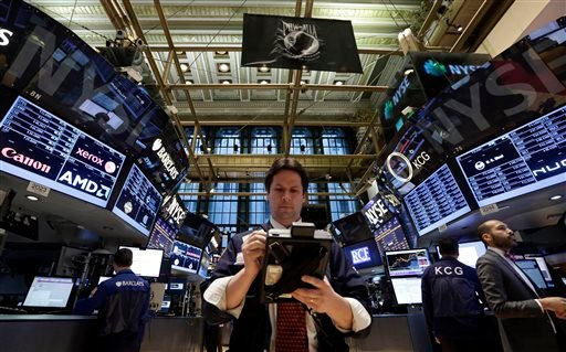 In this Thursday, Jan. 30, 2014, file photo, Trader Patrick McKeon, center, works on the floor of the New York Stock Exchange.
