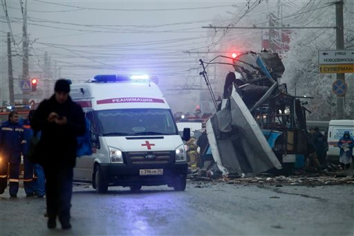 In this Monday, Dec. 30, 2013 file photo an ambulance leaves the site of an explosion after a bomb blast tore through a trolleybus, background, in the city of Volgograd.  (AP Photo/Denis Tyrin, File)