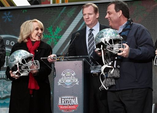 NFL Commissioner Roger Goodell, center, stands between Arizona Gov. Jan Brewer, left, and New Jersey Gov. Chris Christie, right, showoff souvenir football helmets after a ceremony to pass official hosting duties of next year's Super Bowl to Arizona.