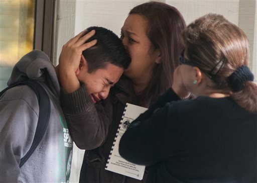In this October 21, 2013 file photo, a Sparks Middle School student is comforted as he cries after being released from Agnes Risley Elementary School, where some students were evacuated to after a shooting, in Sparks, Nev.