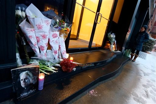 A passer-by stops at a makeshift memorial outside the home of actor Philip Seymour Hoffman, Monday, Feb. 3, 2014, in New York. Hoffman, 46, was found dead Sunday in his apartment of a suspected drug overdose. (AP Photo/Jason DeCrow)
