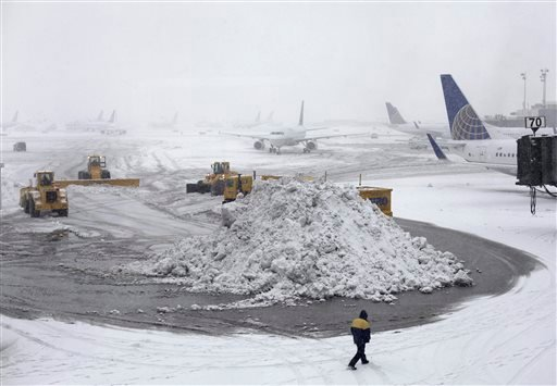 Plows clear runways as snow falls at Newark Liberty International Airport, Monday, Feb. 3, 2014, in Newark, N.J.