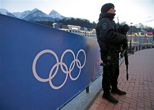 An armed Russian security guard stands at the ski resort Rosa Khutor, where the snow and sliding sports venues for the 2014 Winter Olympics are located, Tuesday, Feb. 4, 2014, in Krasnaya Polyana, Russia. (AP Photo/Dita Alangkara)