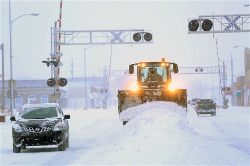 A City of Hutchison, Kan., front end loader clears snow from intersections on S. Main St. Tuesday, Feb. 4, 2014. (AP Photo/The Hutchinson News, Travis Morisse)