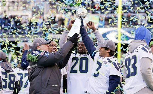 Seattle Seahawks team owner Paul Allen, left, holds up the Vince Lombardi Trophy with Russell Wilson (3) as Korey Toomer and Jeremy Lane (20) react at a rally following a parade for the NFL football Super Bowl XLVIII champions.