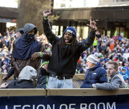 Seattle Seahawks' Richard Sherman, on the Legion of Boom truck, waves to the crowd during the parade for the NFL football Super Bowl champions in Seattle on Wednesday, Feb. 5, 2014.