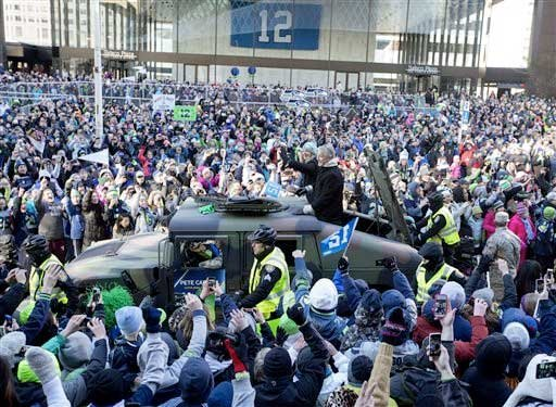 Seattle Seahawks coach Pete Carroll waves to the crowd during a parade for the NFL football Super Bowl champions on Wednesday, Feb. 5, 2014, in Seattle.