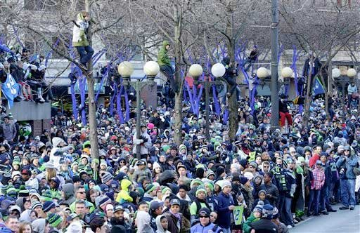 Seattle Seahawks fans watch as the Seahawks pass by during the parade for the NFL football Super Bowl champions on Wednesday, Feb. 5, 2014, in Seattle.