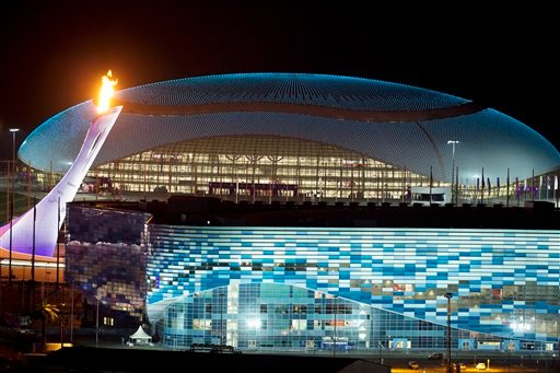 The Olympic Cauldron, left, is lit during a test between the Bolshoy Ice Dome, top, and the Iceberg Skating Palace, foreground, early Thursday morning, Feb. 6, 2014, in Sochi, Russia prior to the start of the 2014 Winter Olympics.(AP Photo/Pavel Golovkin)