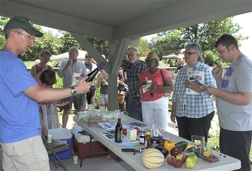 In this June 23, 2012 photo, Michigan State University professor of entomology Rufus Isaacs, left, talks to visitors at Bee-Palooza event in East Lansing, Mich.(AP Photo/Lansing State Journal, Robert Killips)
