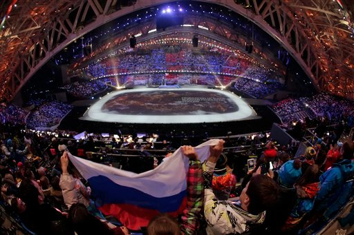 Spectators wave the Russian flag during the opening ceremony of the 2014 Winter Olympics in Sochi, Russia, Friday, Feb. 7, 2014.