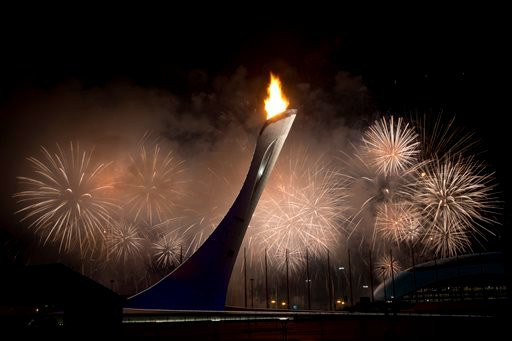 Fireworks explode behind the Olympic torch after it was lit at end of the opening ceremony for the 2014 Winter Olympics in Sochi, Russia, Friday, Feb. 7, 2014.