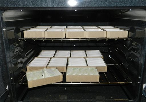 In this Jan. 30, 2014 photo provided by New York City's Office of the Special Narcotics Prosecutor, an oven loaded with bricks of heroin is located in a Bronx apartment during a police raid of the location.