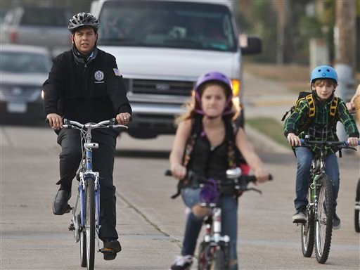 In a Thursday, Jan. 30, 2014 photo, San Diego Mayoral candidate David Alvarez, right, rides through traffic with children and parents headed to school, in San Diego.
