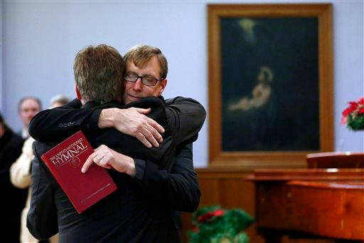 In this Monday, Dec. 16, 2013 file photo, the Rev. Robin Hynicka, right, embraces the Rev. Frank Schaefer, a United Methodist clergyman convicted of breaking church law for officiating at his son's same-sex wedding.