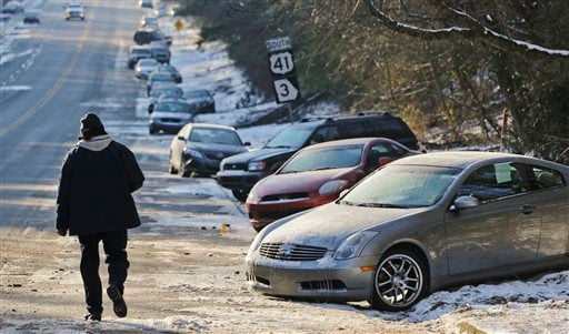 In this Thursday, Jan. 30, 2014, file photo, cars abandoned during an earlier snowstorm sit idle along Northside Parkway in Atlanta.