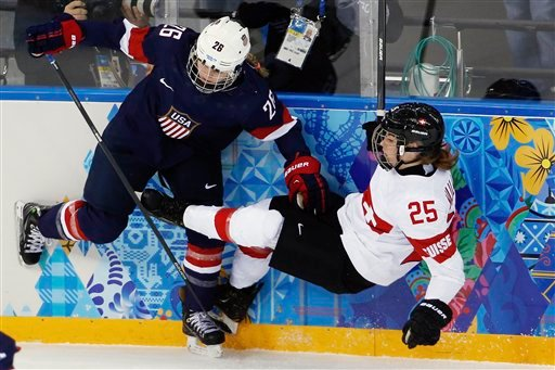 Kendall Coyne of the Untied States collides with Alina Muller of Switzerland against the boards during the first period of the 2014 Winter Olympics women's ice hockey game at Shayba Arena, Monday, Feb. 10, 2014, in Sochi, Russia.