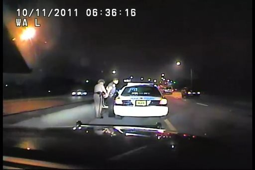 In this frame grab made from an Oct. 11, 2011 video available from the Florida Department of Highway Safety and Motor Vehicles, Florida Highway Patrol Officer Donna Jane Watts arrests Miami Police Department Officer Fausto Lopez.
