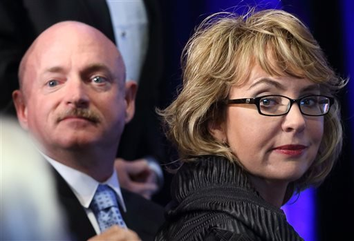 In this Sunday, May 5, 2013, file photo, former U.S. Rep. Gabrielle Giffords, right, and her husband, Capt. Mark Kelly, look back at the crowd after arriving at a ceremony awarding Giffords the John F. Kennedy Profile in Courage Award at the JFK Library.