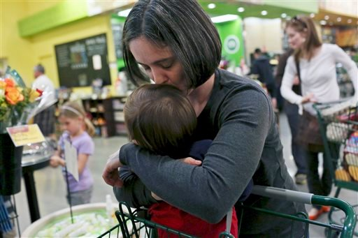 In this Feb. 8, 2014 photo, Nicole Dimetman kisses her son while waiting in the checkout line at Whole Foods in Austin, Texas. (AP Photo/The San Antonio Express-News, Lisa Krantz)