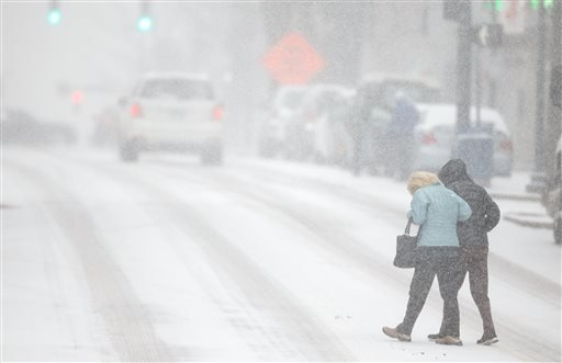 Pedestrians support each other as they cross S. Elm St. during a snow storm, Wednesday, Feb. 12, 2014 in Greensboro, N.C. (AP Photo/News & Record, Jerry Wolford)